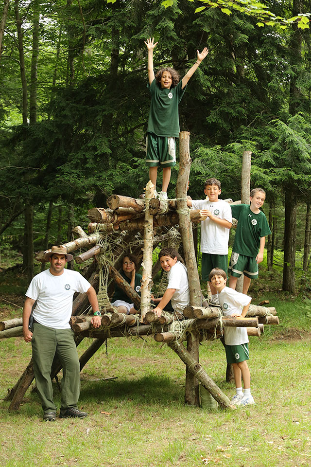 Boys build a survival structure in the woods