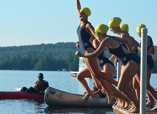 Girls jump into the lake to start the 2 mile swim