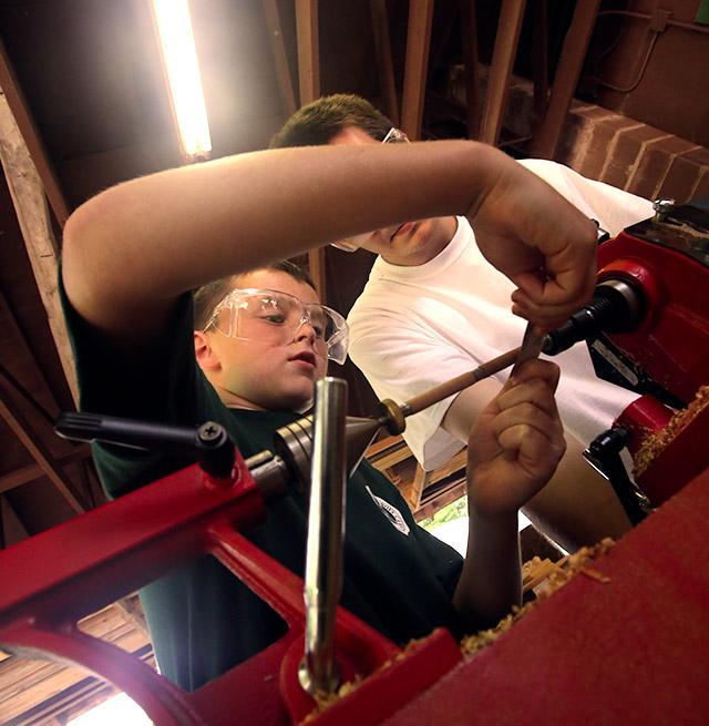 A boy learns how to use a lathe from a teacher