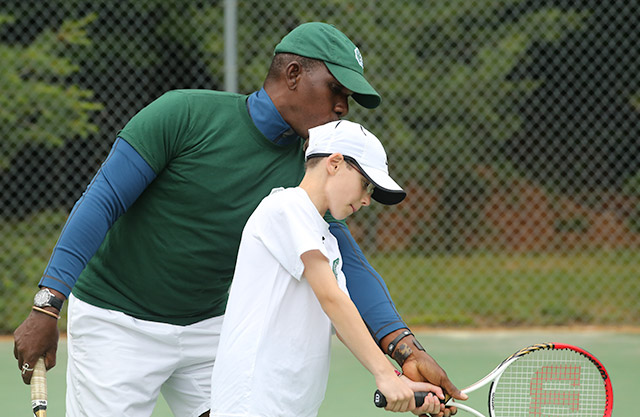 A mentor teaches a boy about tennis