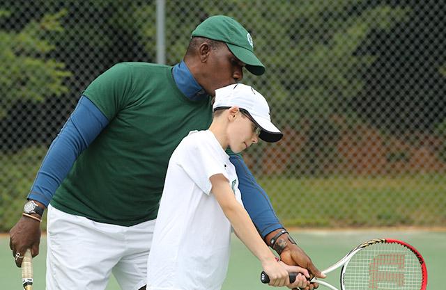 A mentor teaches a boy about tennis