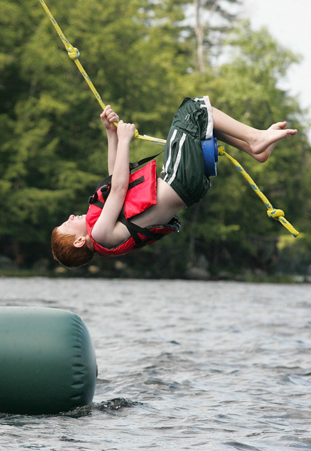 A boys swings upside down over the water