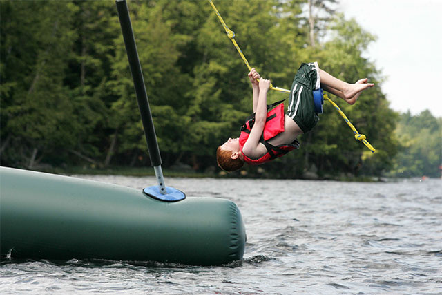 A boy swimgs out over the lake on a rope swing