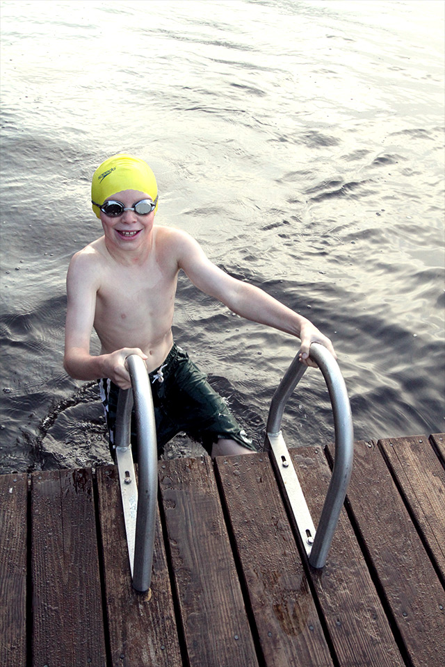 At last, the swim is complete and a smiling boy climbs the ladder on to the girls dock