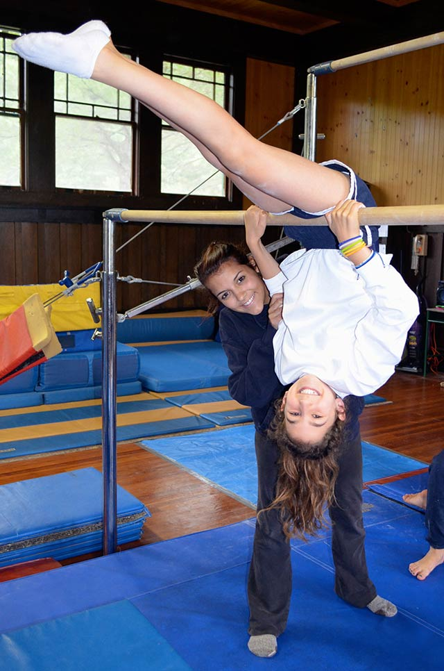 A teacher with a girl on uneven parallel bars