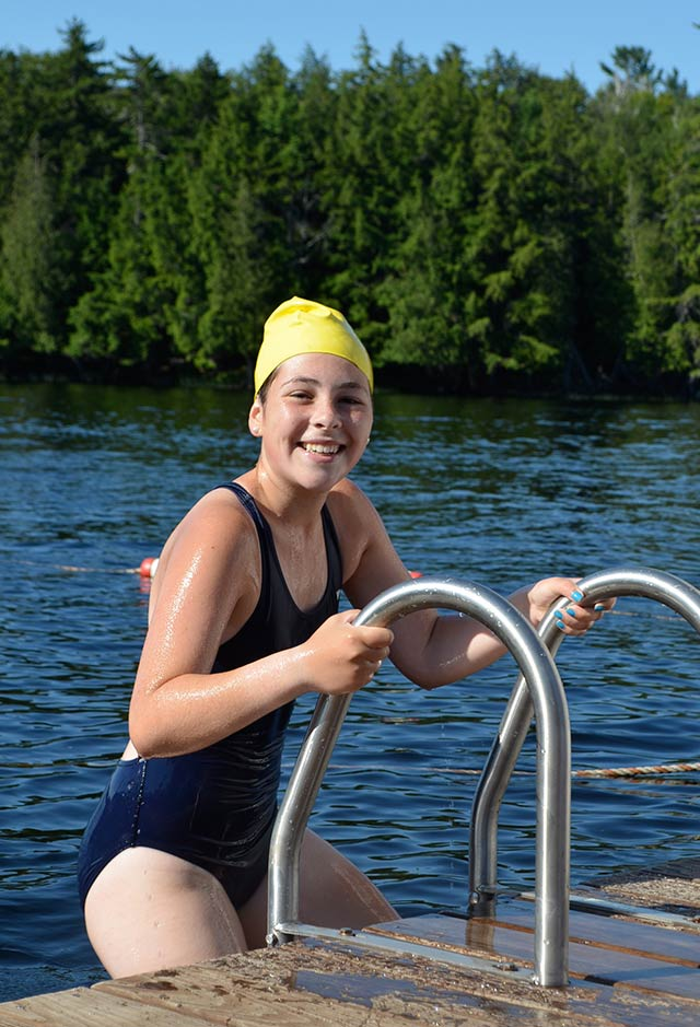 At last, the swim is complete and a smiling girl climbs the ladder on to the boys dock